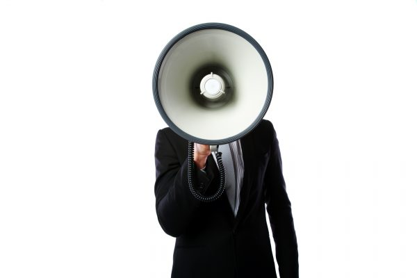 Businessman with megaphone standing isolated on a white background